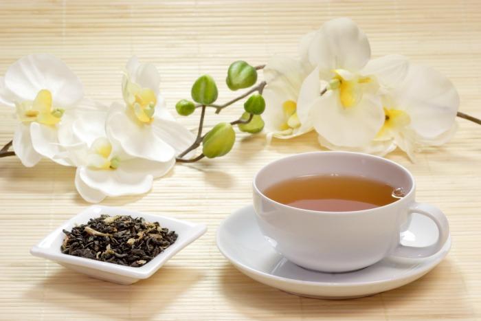 Cup Of Jasmine Tea Wih Tea Leaves In A Bowl
